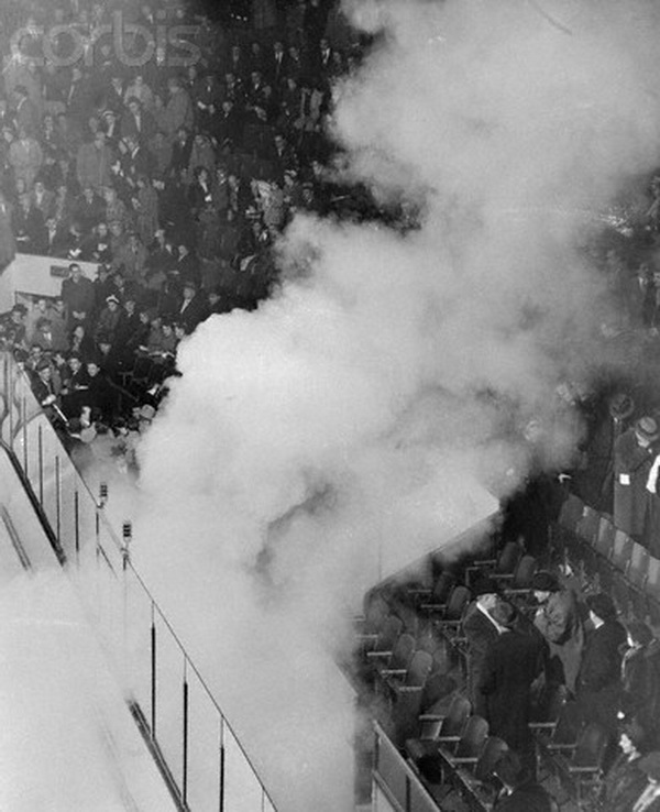 "17 Mar 1955, Montreal, Canada --- Smoke rising from a tear gas bomb drifts through the Forum arena March 17 as 15, 000 demonstrators angrily protest the suspension of Maurice ""The Rocket"" Richard by National Hockey League President Clarence Campbell. The bomb was set off by a demonstrator at the intermission between the first and second periods. It was at this point that Fire Chief Armand Pare ordered the game halted for the ""protection of the people."" Montreal trailed at the time, 4-1, and that was declared the final score. The calm of the spectators in the upper seats, which were unaffected by the bomb's fumes, prevented crushing at the exits. --- Image by © Bettmann/CORBIS"